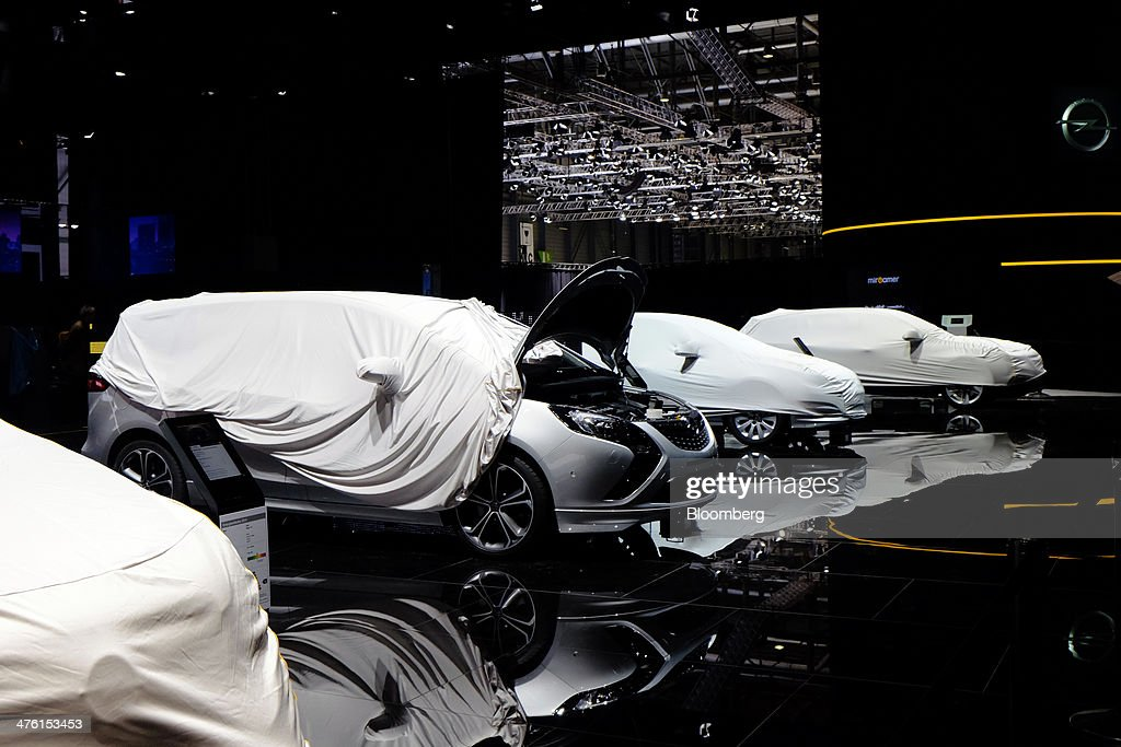 Protective covers sit over Opel automobiles, produced by General Motors Co. (GM), during preparations ahead of the 84th Geneva International Motor Show in Geneva, Switzerland, on Sunday, March 2, 2014. The International Geneva Motor Show will run from March 4 and showcase the latest models from the world's top automakers. Photographer: Gianluca Colla/Bloomberg via Getty Images