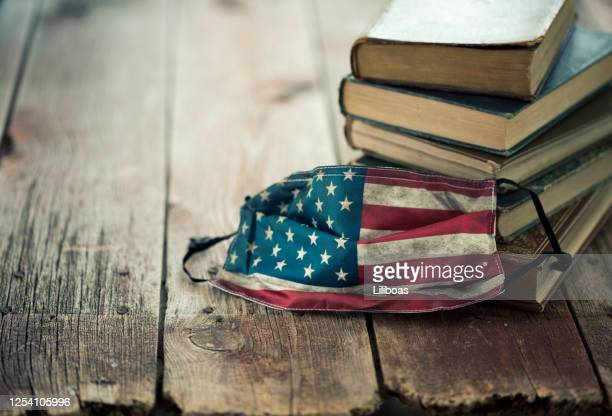 protective face mask and stack of books - graphic print stock pictures, royalty-free photos & images