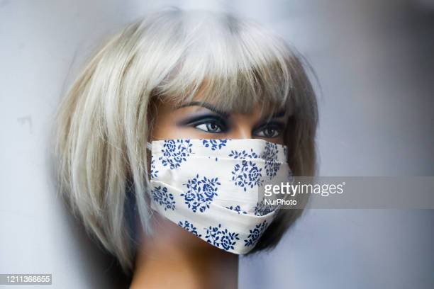 Protective face mask is seen on a mannequin at fashion shop window during the spread of coronavirus. Krakow, Poland on April 29, 2020. The rule of...
