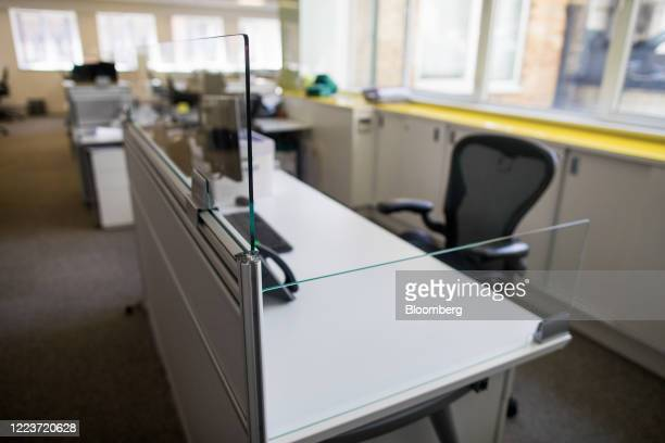 Protective glass screens surround a workstation at offices in London, U.K., on Wednesday, June 24, 2020. Companies are getting ready to welcome more...
