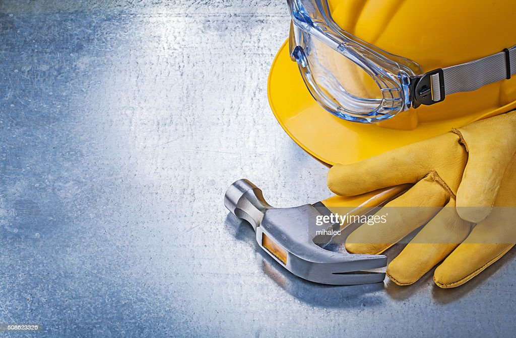 Protective glasses gloves building helmet claw hammer on metalli : Stock Photo