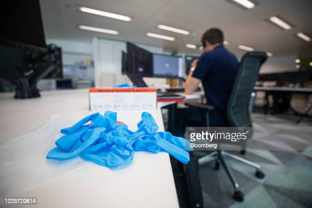 Protective gloves sit on a desk next to an employee at Cushman & Wakefield Plc's offices during the first phase of the reoccupation of their...