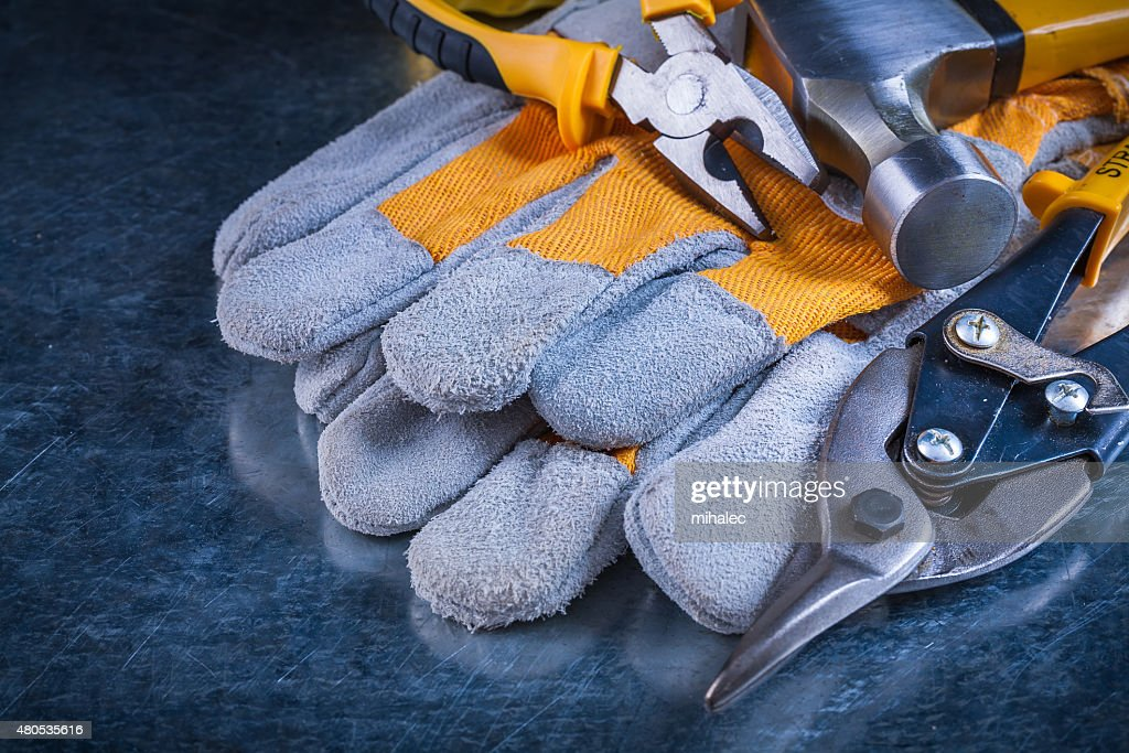 Protective gloves with claw hammer pliers and tin snips on : Stock Photo