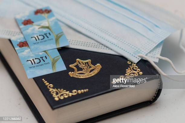 Protective masks and Israel Memorial Day 'Yizkor' stickers rest on top of an Israel Defense Forces Hebrew bible amid the coronavirus pandemic on...