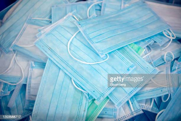 Protective masks sit in a pile at the Mask Factory Co facility in Hong Kong China on Tuesday Feb 25 2020Hong Kong's government unveiled on Feb 26 a...