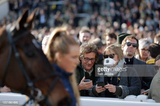 A protective medical mask wearer during day four of the Cheltenham National Hunt Racing Festival at Cheltenham Racecourse on March 13th 2020 in...