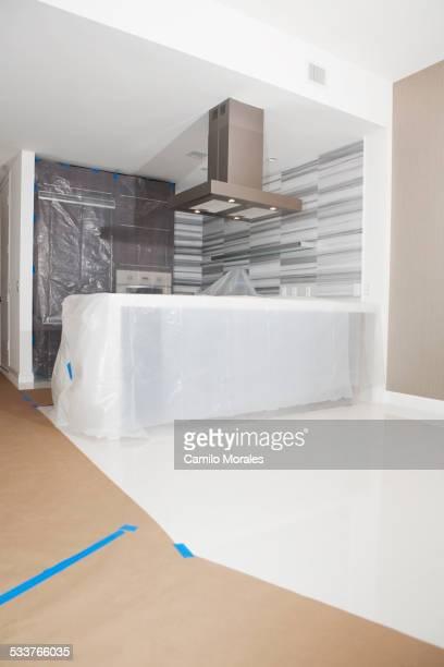 protective plastic and paper tarps in kitchen under renovation - afzuigapparaat stockfoto's en -beelden
