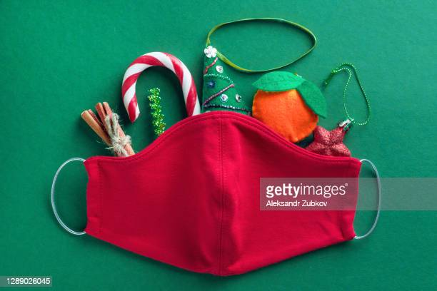 protective red medical face mask, striped sweet candy cane, handmade christmas tree toys, cinnamon, tinsel on green background. prevention and prevention of the spread of the covid 19 pandemic. the concept of a happy healthy christmas. - illness prevention stock pictures, royalty-free photos & images