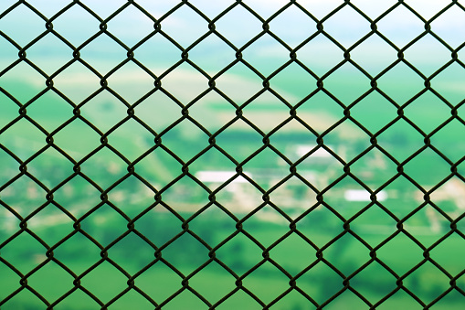 Protective restrictive metal mesh on top of the mountain. Beautiful view of the green summer valley from the top of the mountain 1135205333