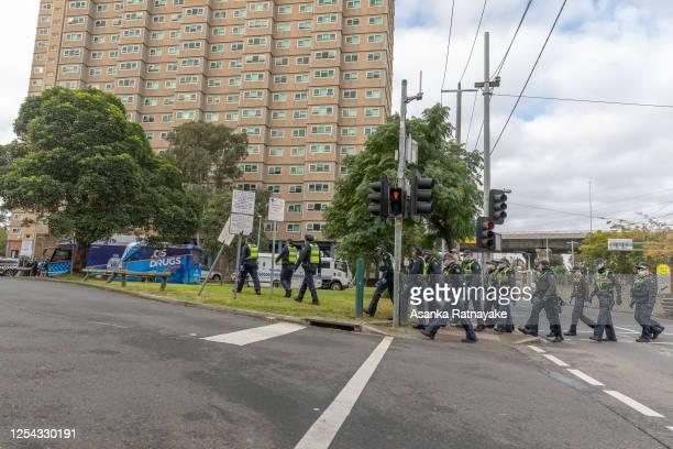 Protective service police officers walk towards the Flemington Public housing flats on patrol on July 05, 2020 in Melbourne, Australia. Nine public...