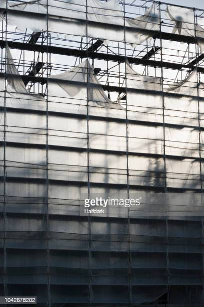 protective sheeting over highrise building under construction - 防水シート ストックフォトと画像