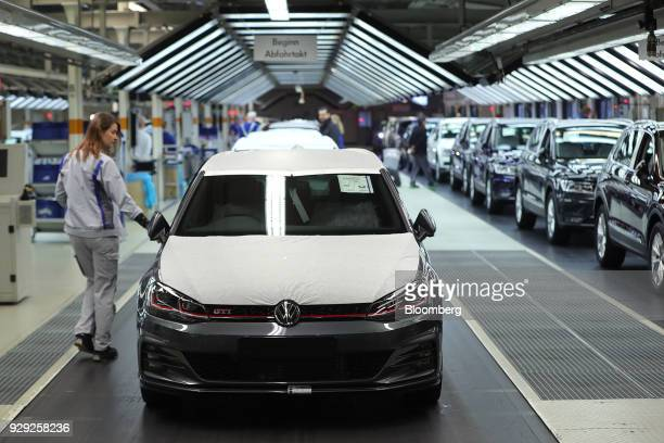 Protective sheets cover the hood and roof panel of a Volkswagen AG Golf GTI automobile as an employee makes final quality checks at the VW factory in...