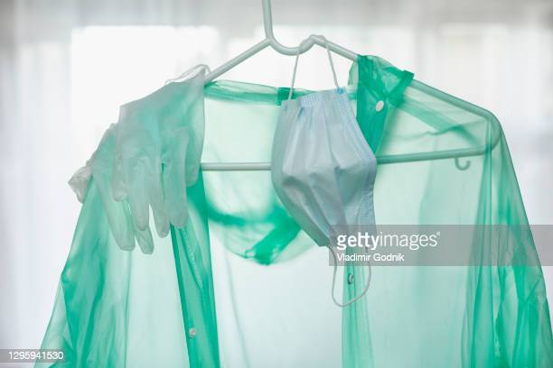 protective suit, gloves and face mask hanging on hanger - essential services stock pictures, royalty-free photos & images