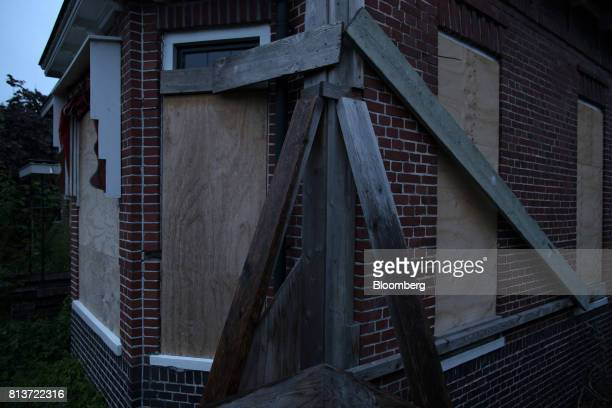 Protective wooden boards stand over the windows of an uninhabitable house affected by fracking in Woldendorp Groningen Netherlands on Friday June 30...