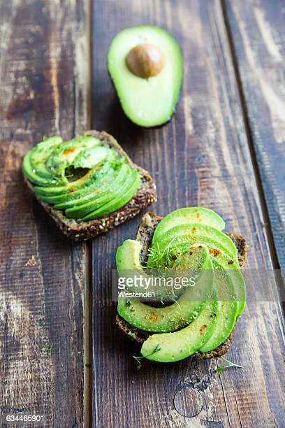 Protein bread garnished with sliced avocado, cress and chili powder