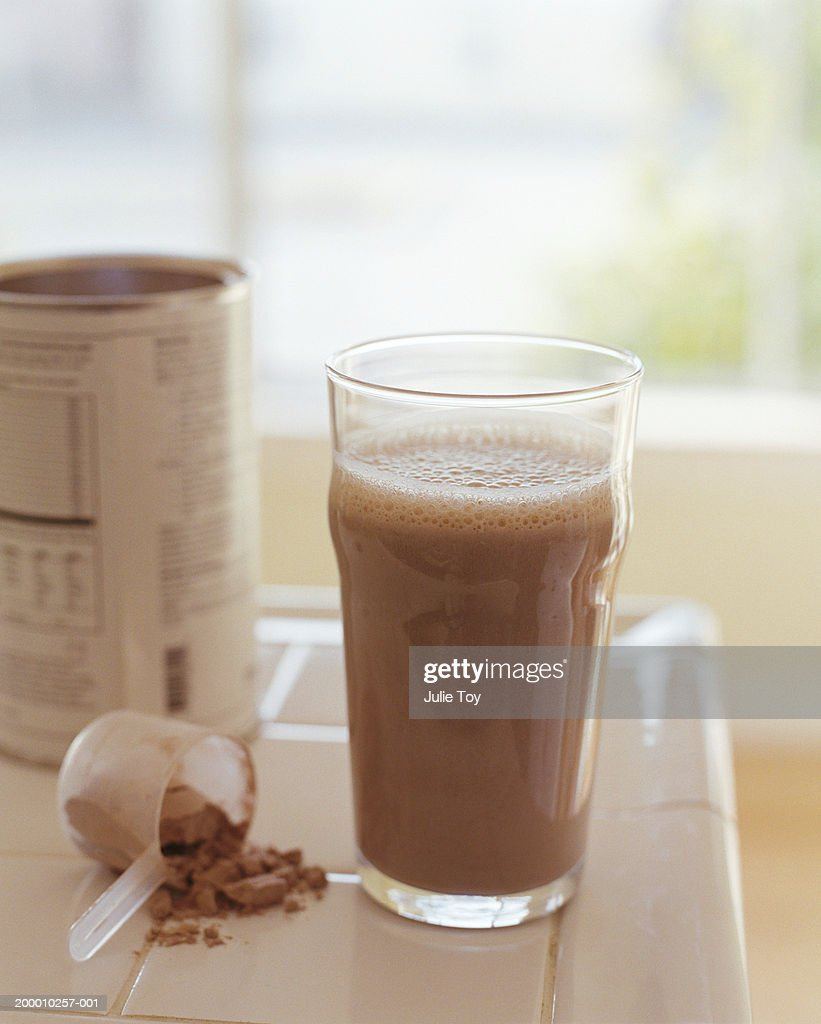 Protein drink with can and measuring cup on counter : Stock Photo