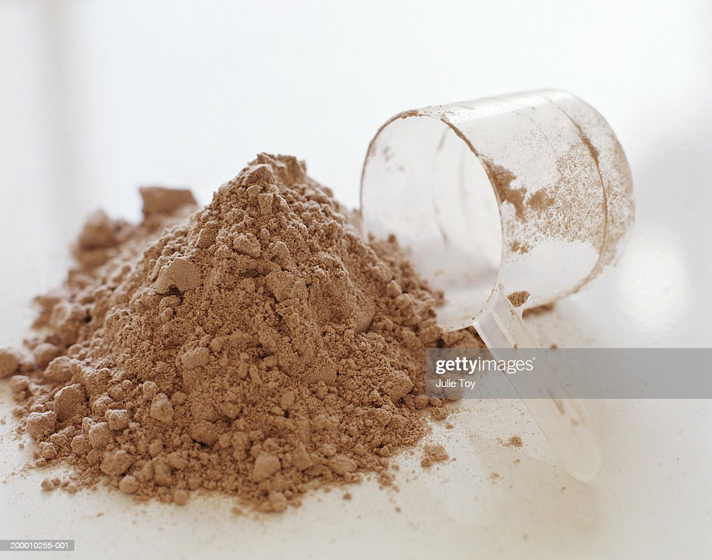 Protein powder and measuring cup : Stock Photo