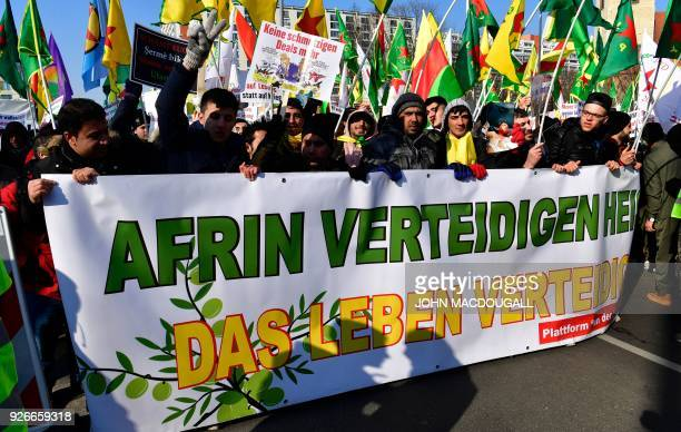 Protersters hold a giant banner reading 'To defend Afrin means to defend life' during a demonstration of Kurdish groups to protest against Turkey's...