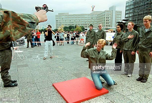 Protest gegen die jaehrlichen Geloebnisse der Bundeswehr auf dem Alexanderplatz in Berlin: eine Gruppe von Gegnern des Gelöbnisses nimmt verkleidet...