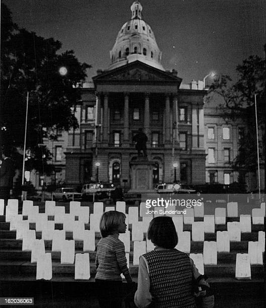 Protest In Lights A prates A young girl and her mother talk in front of illuminated tombstones set up on the west steps of the Capitol Tuesday...
