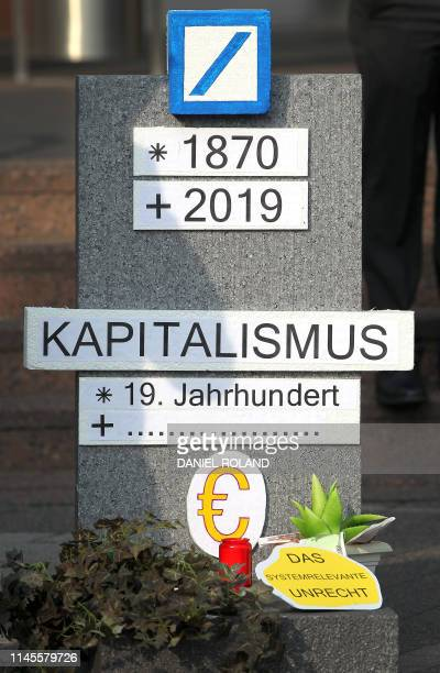 A protest intervention with a tomb stone mockup showing the logo of the German company Deutsche Bank is pictured in front of the Messehalle prior to...