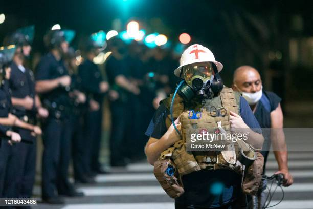 Protest medic walks near police as demonstrations continue over the killing of George Floyd despite the dangers of the widening coronavirus pandemic...