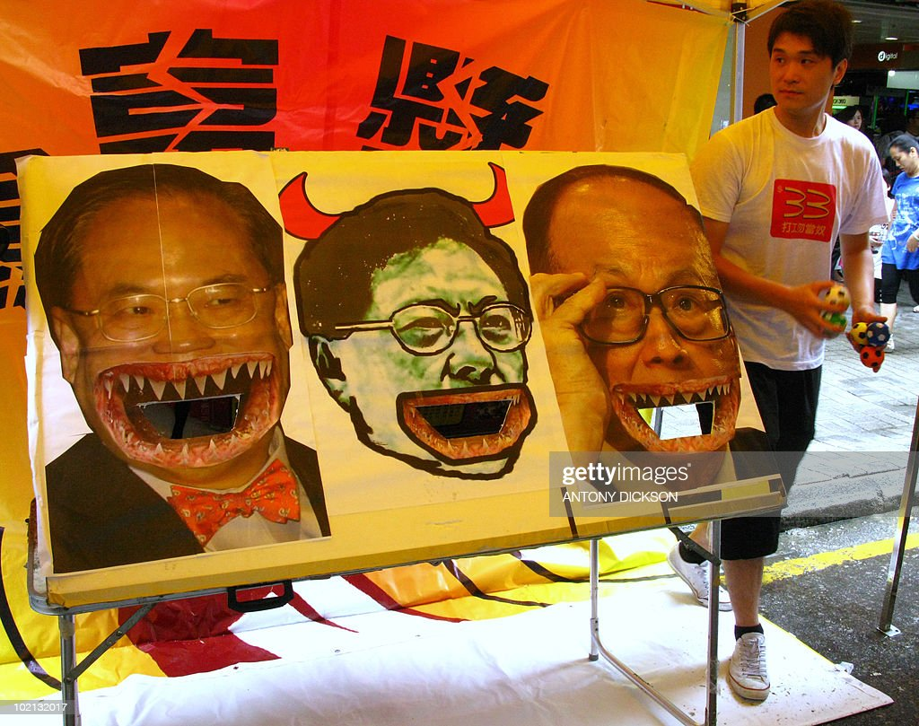 S SURNAME A protest organiser stands next to pictures of (L-R) Hong Kong Chief Executive Donald Tsang, catering sector legislator Tommy Cheung Yu-yan and leading businessman Li Ka-shing, into whose mouths balls are to be thrown, during a minimum wage demonstration in Hong Kong on June 13, 2010. The rally, organised by the Hong Kong Confederation of Trade Unions and the People's Alliance for Minimum Wage, was to promote the introduction of a universal minimum wage in Hong Kong of 33 HKD (4.25 USD) per hour. Cheung has become a hate figure among low paid workers and other unionists for suggesting last month that the minimum wage, to be implimented in 2011, should be set at an hourly rate of just 20 HKD. AFP PHOTO / Antony DICKSON