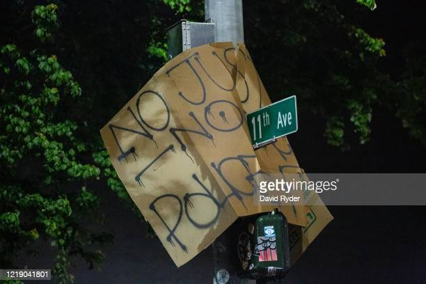 Protest sign is seen on a street sign near the Seattle Police Departments East Precinct on June 9, 2020 in Seattle, Washington. Protests have...