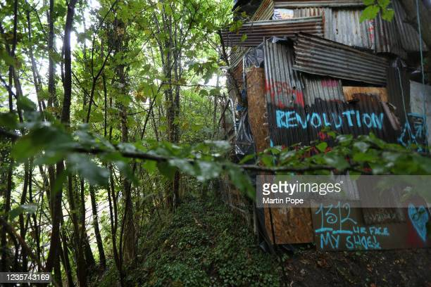 Protest tower made from corrugated iron panels and pallets and decorated with graffiti stands between the A413 road and the existing rail line on...