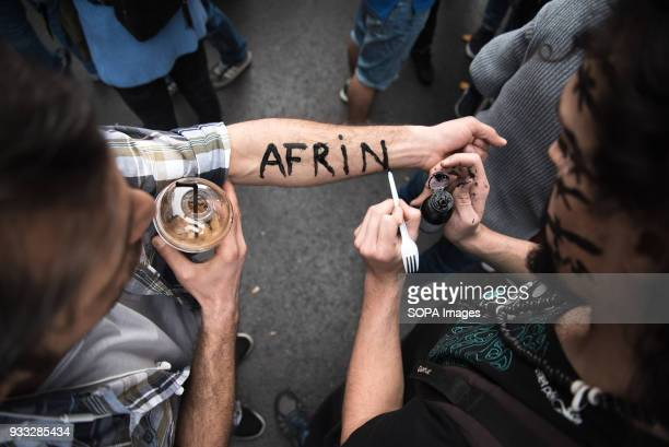 Protestant painting on another protester's hand with the word 'Afrin' in solidarity of the Kurdish people being attacked by the Turkish government...
