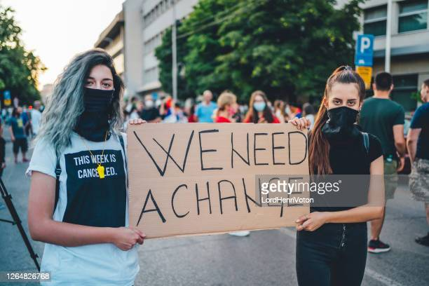 protestant women holding a poster - weakness stock pictures, royalty-free photos & images