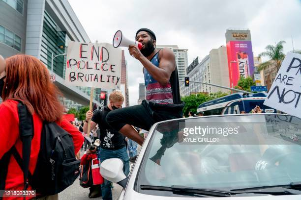 A protester addresses the crowd as they march through downtown during a demonstration over the death of George Floyd while in Minneapolis Police...