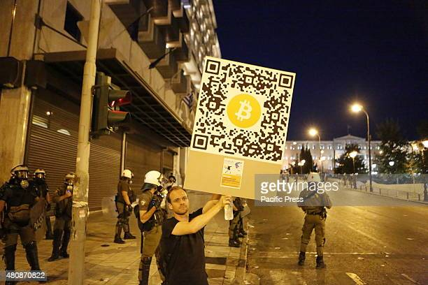 SQUARE ATHENS ATTICA GREECE A protester advertises Bitcoin at the antiausterity protest outside the Greek Parliament in Athens Molotov cocktails tear...