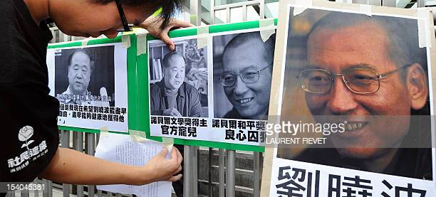 A protester affixes pictures of Chinese writer Mo Yan and Chinese dissident Liu Xiaobo to a gate during a demonstration in front of the Chinese...