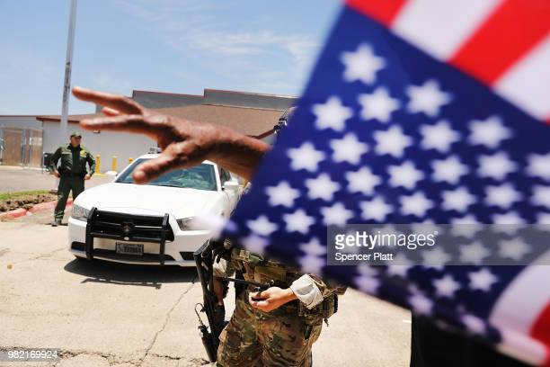 A protester against the Trump administration's border policies argues with a Border Patrol agent during a rally at the US Customs and Border...
