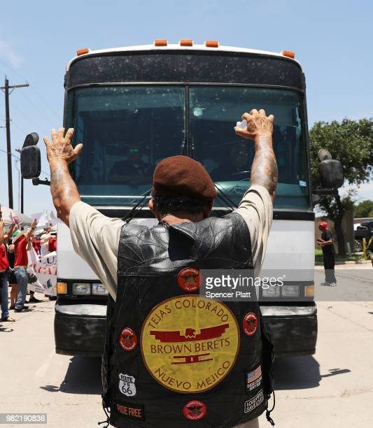 A protester against the Trump administration's border policies tries to block a bus carrying migrant children out of a US Customs and Border...