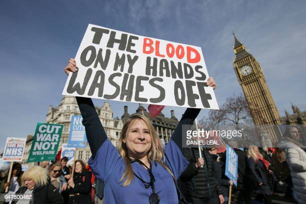 A protester an NHS doctor holds a placard up in front of the Elizabeth Tower also known as Big Ben at the Houses of Parliament during a march against...