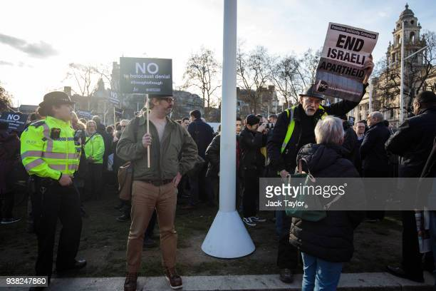 A protester and counterprotester hold placards as they attend a demonstration in Parliament Square against antiSemitism in the Labour Party on March...