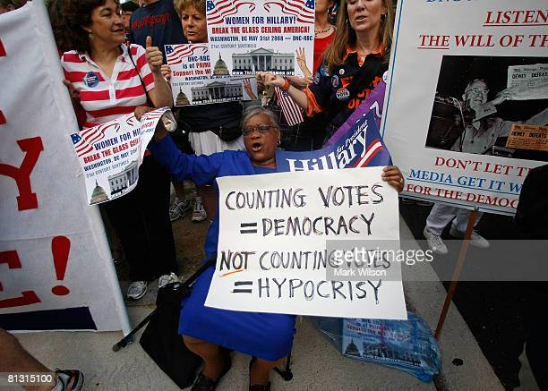 Protester Annette Sanon holds a sign saying counting votes equals democracy not counting votes equals hypocrisy while demonstrating in front of the...