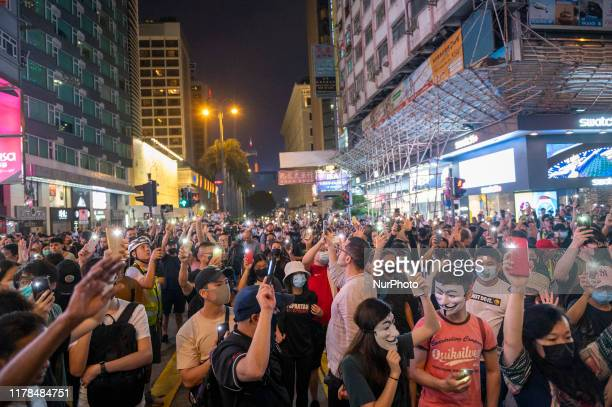 Protester are seen holding up their cellphone tourches during an AntiGovernment Protest in Tsim Sha Tsui district in Hong Kong China October 27...