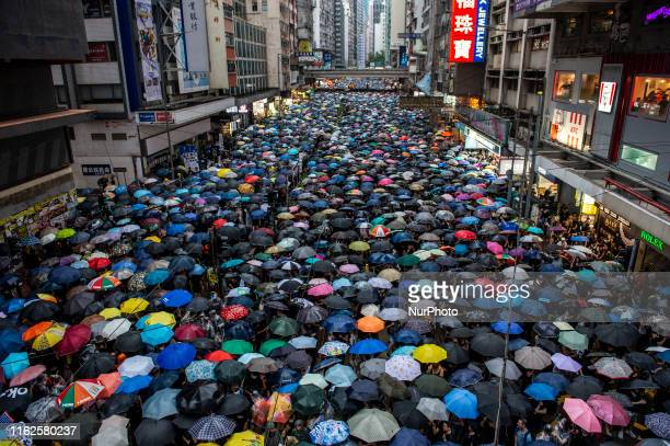 Protester are seen holding up umbrellas while they walk down a street in Hong Kong on August 18 Tens of Thousands take to the streets of Hong Kong in...