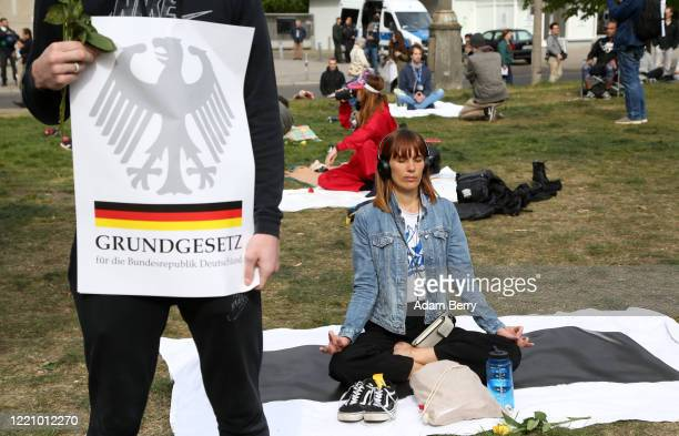 Protester, attempting to show she is peaceful, meditates as another holds a sign referring to the Grundgesetz, or German constitution known as the...