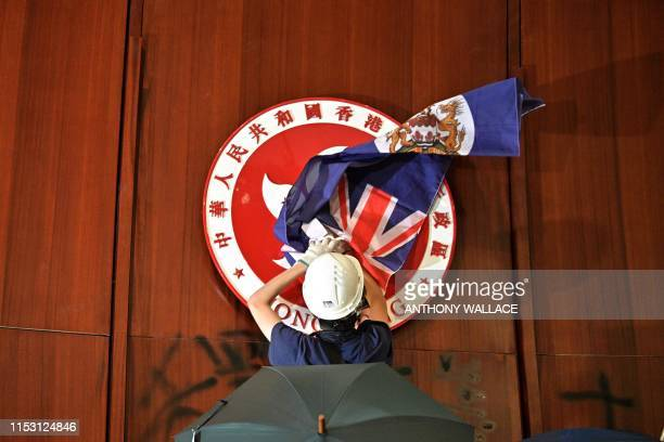 TOPSHOT A protester attempts to cover the Hong Kong emblem with a British colonial flag after they broke into the government headquarters in Hong...