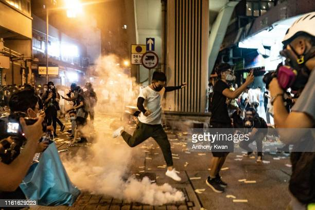 A protester attempts to kick a tear gas canister during a demonstration on Hungry Ghost Festival day in Sham Shui Po district on August 14 2019 in...