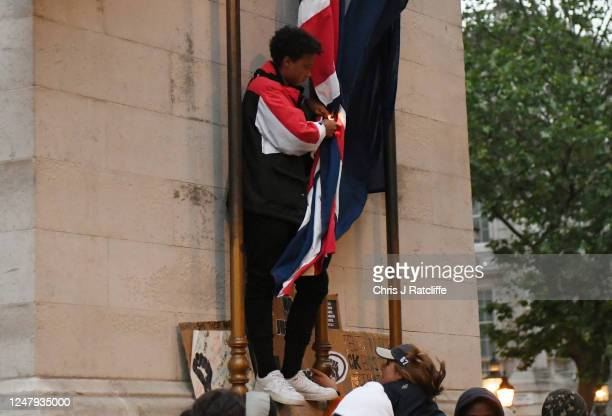 Protester attempts to set fire to the flags on the Cenotaph memorial during a Black Lives Matter protest on June 07, 2020 in London, United Kingdom....