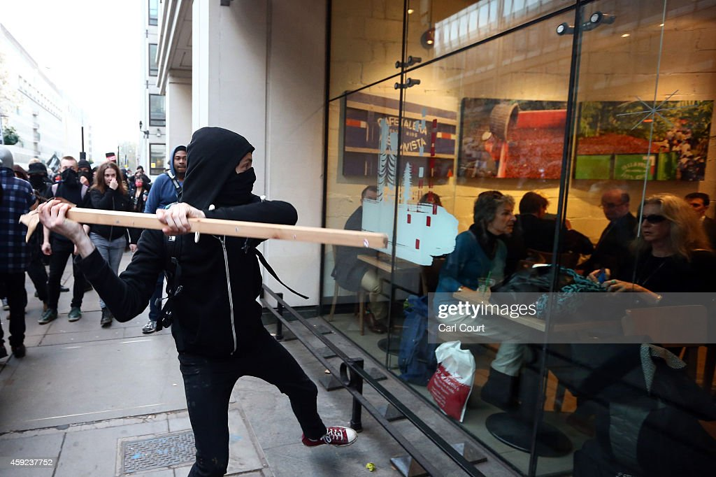 A protester attempts to smash a Starbucks window during a demonstration against fees and cuts in the education system on November 19, 2014 in London, England. A coalition of student groups have organised a day of nationwide protests in support of free education and to campaign against cuts. Photo by Carl Court/Getty Images)