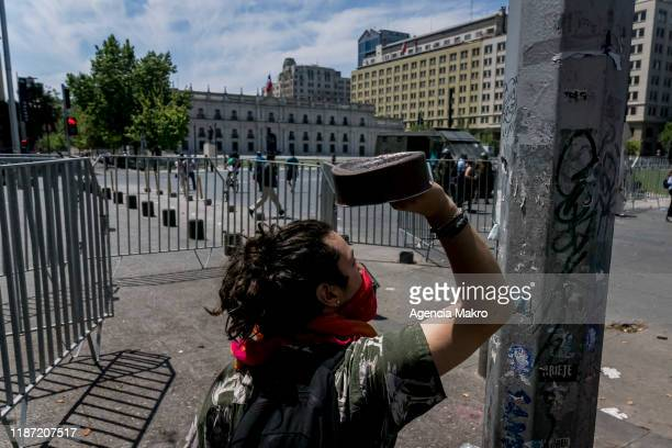 Protester bangs a pot against a lamppost in front of La Moneda Palace during a national strike and general demonstration called by different workers...