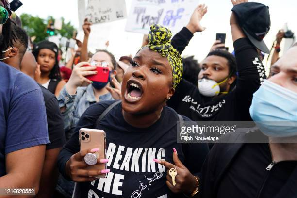 A protester becomes emotional while taking part in a conversation with a police officer during a demonstration on May 31 2020 in Atlanta Georgia...