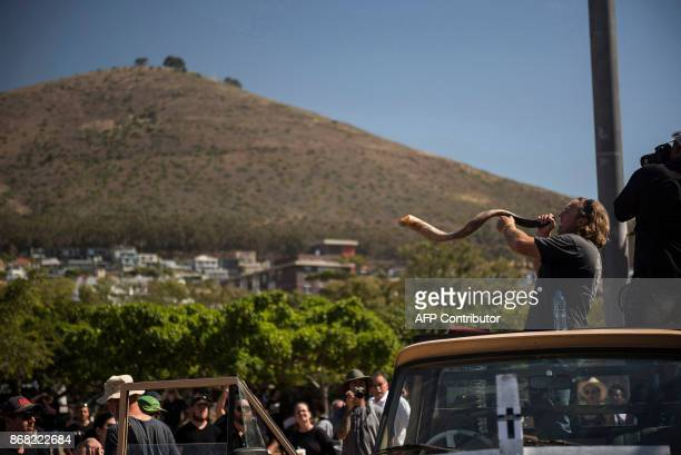 A protester blows a horn as South African farmers farm workers attend a demonstration at the Green Point stadium to protest against farmer murders in...