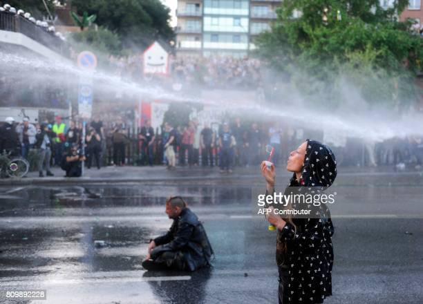 A protester blows bubbles as riot police use water cannons during during the 'Welcome to Hell' rally against the G20 summit in Hamburg northern...